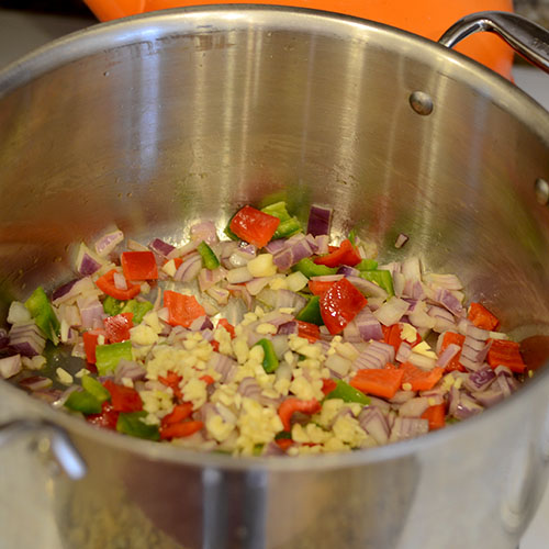 Vegetables in pot, red onion, peppers, garlic,