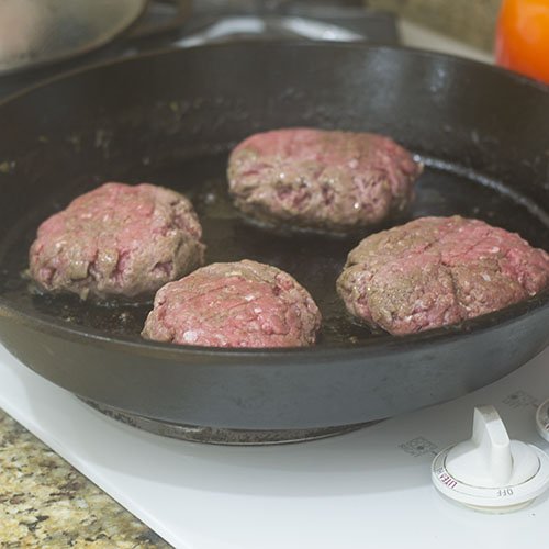 Burgers Cooking in Cast Iron Skillet
